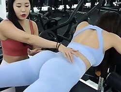 Two morose Korean fitness models having fun working out